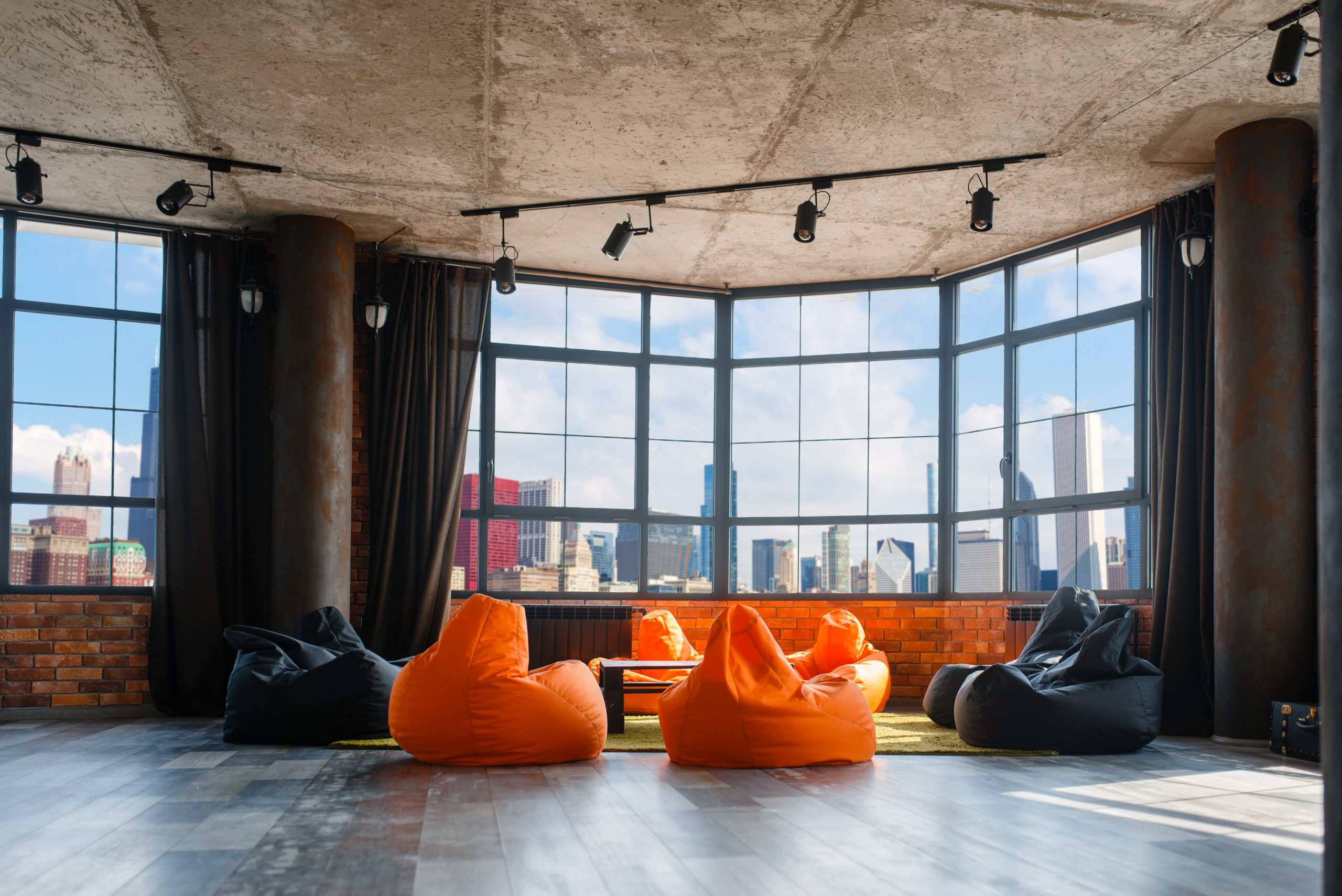 Apartment studio with panoramic cityscape view, nobody. Living roomin grunge style with big windows, coffee table and modern chairs, downtown city with skyscrapers on background, panorama